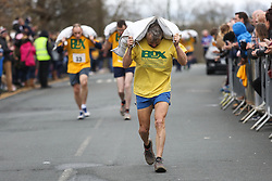 © Licensed to London News Pictures. 28/03/2016. Gawthorpe, UK. Competitors struggle with their 50kg bags of coal as they approach the finish during the 2016 World Coal Carrying Championships. The championships are held annually on Easter Monday in the small West Yorkshire town of Gawthorpe. The competition is a race which involves carrying a 50kg bag of coal up a steep incline to the finish line. Photo credit : Ian Hinchliffe/LNP
