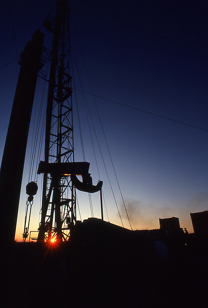 Low angle view of silhouetted on-shore oil drilling rig at sunset in Texas.