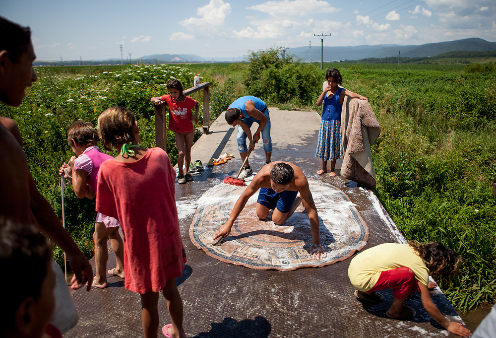 """Young men cleaning carpets on a bridge across river """"Bodva"""" close to their Roma settlement """"Budulovska Street""""  in Moldava nad Bodvou. The city has roughly 11200 inhabitants, about 1980 (18%) of them have Roma ethnicity and around 800 are living at the segregated settlement 'Budulovska Street' (2014)."""