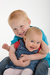 Portrait of a baby sister and brother in the studio laughing,