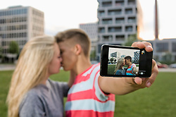 Teenage couple taking self portrait with themselves