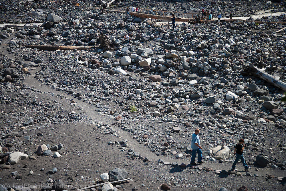 Visitors hike along a trail in the Nisqually River riverbed in Mount Rainier National Park, Washington, USA