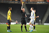 Milton Keynes Dons midfielder Brennan Dickenson (11) shown a yellow card, booked  during the EFL Trophy match between Milton Keynes Dons and Coventry City at Stadium:MK, Milton Keynes, England on 3 December 2019.