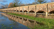 Arches of Maud Heath's causeway reflected by flood water, Kellaways, Wiltshire, England, UK