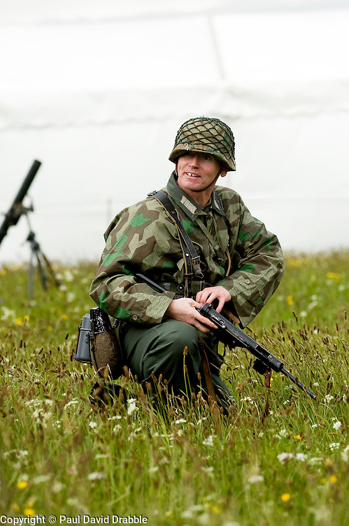 Member of the Northern World War Two Association. Portraying a soldier from 21st Panzer Division clears his jammed MP40 during a large scale Western Front  battle reenactment. .Scarborough.Sunday 30th May 2010 .Images © Paul David Drabble.