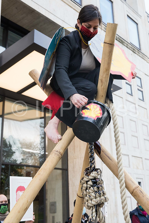An environmental activist from Extinction Rebellion pours fake oil from a bucket on top of a tripod outside the Shell Centre on the 25th anniversary of the killings of the Ogoni Nine on 10 November 2020 in London, United Kingdom. The Ogoni Nine, leaders of the Movement for the Survival of the Ogoni People (MOSOP) including activist Ken Saro-Wiwa, were executed by the Nigerian government in 1995 after having led a series of peaceful marches involving an estimated 300,000 Ogoni people against the environmental degradation of the land and waters of Ogoniland by Shell and to demand both a share of oil revenue and greater political autonomy.