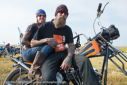 Pinky and Long Jon Barwood at the Ross Thomas memorial at the Broken Spoke County Line during the Sturgis Black Hills Motorcycle Rally. SD, USA. August 4, 2014.  Photography ©2014 Michael Lichter.