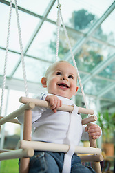 Portrait of smiling toddler sitting in a swing