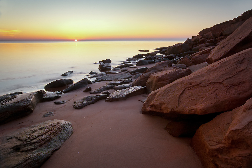 This photograph was made in Prince Edward Island National Park in a small less visited cove. I had been on a commercial home shoot and extended my stay so I could do some traveling and personal photography. I found this cove from another photographer's tip and arrived early before sunrise. The red rocks of PEI were used as a compositional frame to lead the eye out to the ocean, as the sun rose just ever so slightly above the horizon. Although shooting into the sun is considered not a good practice, I believe in breaking the rules and doing the unexpected.