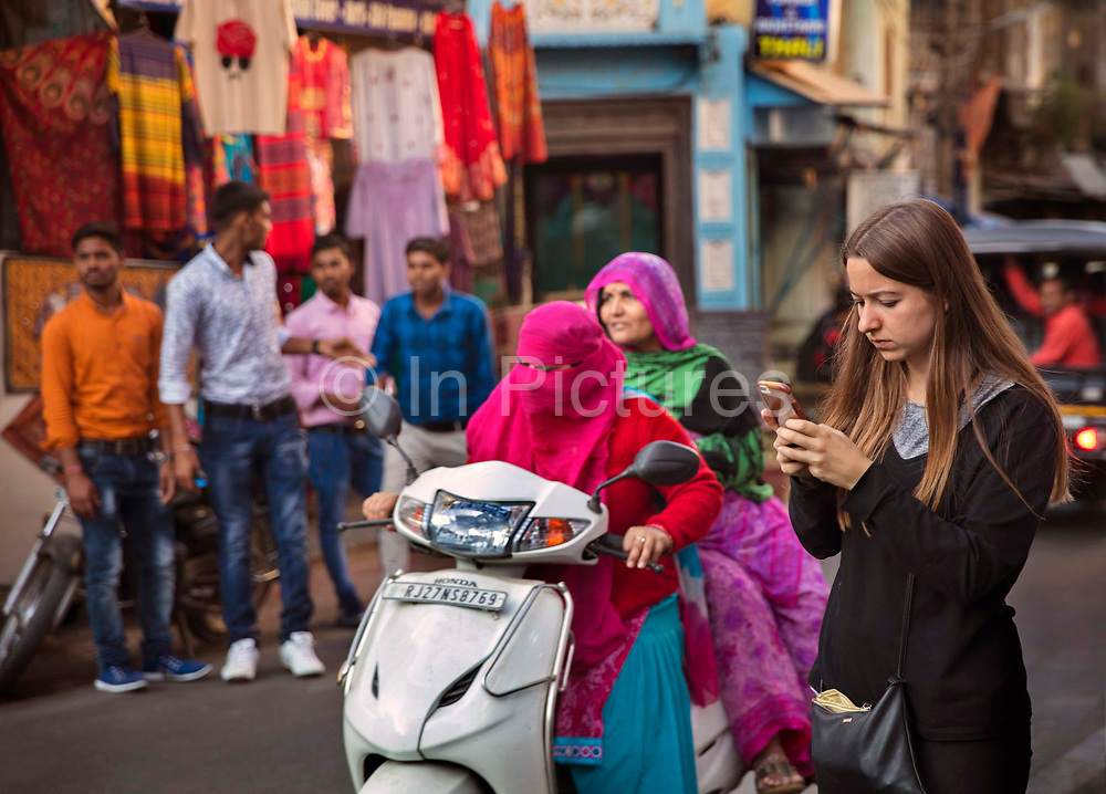 A female western tourist using her mobile phone on the 20th January 2018  in the city of Udaipur, India. Behind her 2 Rajasthani women with traditional saris and veils share a scooter in the busy traffic.