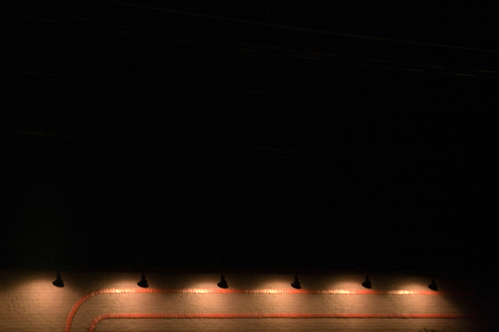 Bright spotlights create the illusion of a stage on a brick wall.