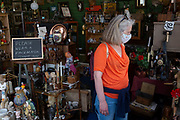 A lady wearing a face covering browses for collectable bargains in an antiques shop that is asking for its customers to wear appropriate face coverings during the Coronavirus pandemic lockdown, on 11th July 2020, in Bury St. Edmunds, Suffolk, England.