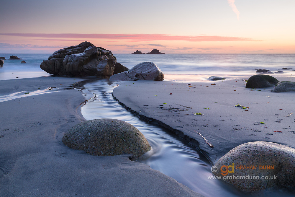 A freshwater stream carves a channel into the sands and enters the sea at Porth Nanven in the Cot Valley, Cornwall. Captured at dusk, low tide waters reflect the sunset colours in the sky. It is a fantastic beach littered with beautifully rounded boulders, otherwise known as 'Dinosaur Egg Beach'. Summer in England, UK. July 2014.