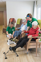 Nurse helping senior women doing exercise on mini foot pedal in rest home