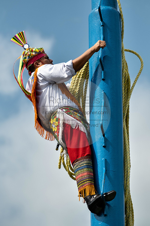 A Volador climbs the thirty-meter pole to perform the sacred ceremonial dance in the Parque Takilhsukut at the pre-Columbian archeological complex of El Tajin in Tajin, Veracruz, Mexico. The Danza de los Voladores is a indigenous Totonac ceremony involving five participants who climb a thirty-meter pole. Four of these tie ropes around their waists and wind the other end around the top of the pole in order to descend to the ground. The fifth participant stays at the top of the pole, playing a flute and a small drum. The ceremony has been inscribed as a Masterpiece of the Oral and Intangible Heritage of Humanity by UNESCO.