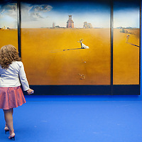 """MILAN, ITALY - SEPTEMBER 21:  A woman admires """"Landscape with girl skipping rope"""", oil painting by Salvador Dali at the Exhibition preview at Palazzo Reale on September 21, 2010 in Milan, Italy. Dali is back in Milan with Il sogno si avvicina, an exhibition that takes place at Palazzo Reale  and that focus on the relationship between the great Spanish artist's visions and his favourite themes:  landscape, dream and desire."""