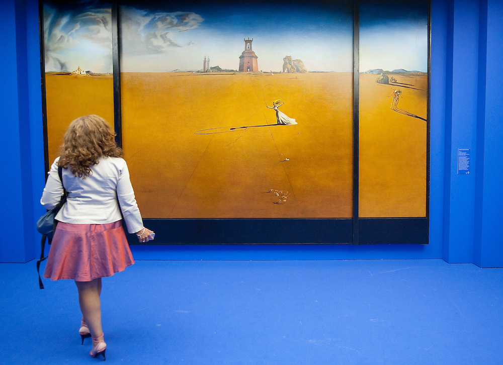 "MILAN, ITALY - SEPTEMBER 21:  A woman admires ""Landscape with girl skipping rope"", oil painting by Salvador Dali at the Exhibition preview at Palazzo Reale on September 21, 2010 in Milan, Italy. Dali is back in Milan with Il sogno si avvicina, an exhibition that takes place at Palazzo Reale  and that focus on the relationship between the great Spanish artist's visions and his favourite themes:  landscape, dream and desire."