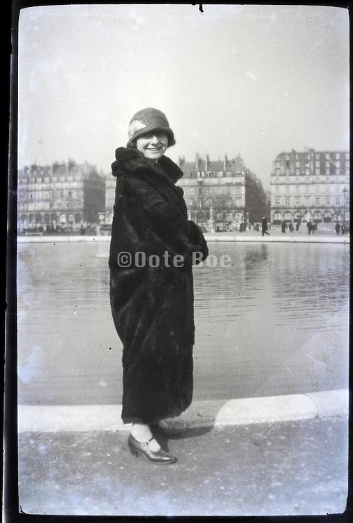 female person wearing fur coat in public park early 1900s Paris