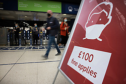 © Licensed to London News Pictures. 07/09/2020. London, UK. Passengers pass a sign at Waterloo Station warning of a £100 fine for not wearing a face covering. Train capacity is supposed to reach 90% today as holidays come to an end and schools return. Photo credit: Peter Macdiarmid/LNP