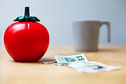 Plastic tomato sauce dispenser next to money and a cup (Credit Image: © Image Source/Julian Ward/Image Source/ZUMAPRESS.com)