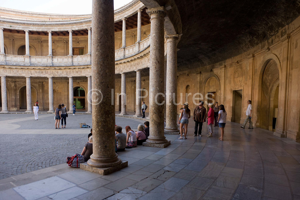 Visitors admire the inner circle of Palacio de Carlos V at Alhambra, Granada. The Palace of Charles V is a Renacentist construction in Granada, southern Spain, located on the top of the hill of the Assabica, inside the Nasrid fortification of the Alhambra. It was commanded by Charles V, Holy Roman Emperor, who wished to establish his residence close to the Alhambra palaces. The plan of the palace is a 63 meter square containing an inner circular patio. This structure, the main Mannerist characteristic of the palace, has no precedent in Renaissance architecture, and places the building in the avant-garde of its time. The circular patio has also two levels. The lower consists of a doric colonnade of conglomerate stone, with an orthodox classical entablature formed of triglyphs and metopes.