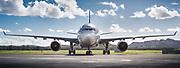 photographie en couleur d'un Airbus de la compagnie aérienne Aircalin présenté de face et sur son Tarmac à l'aéroport international de la Tontouta