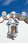 A statue of the Virgin Mary in a niche on the gaily painted facade of Santa Maria de la Asuncion in Tule, Mexico.