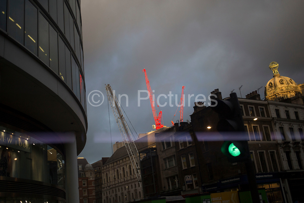 Red cranes lit up in evening light in Moorgate, London, UK. There is an increasing amount of construction all over the city, with a crane above every building.