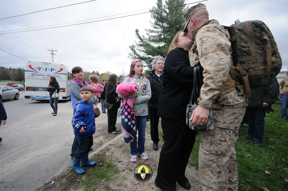 5/5/11 -- TOPSHAM, Maine.  U.S. Marine Lance Cpl John Crowley, of Bath kisses his wife, Kristin goodbye just before getting on the bus and heading for deployment. Marine Reservists departed from Topsham on Thursday for the start of a year-long deployment to Afghanistan amidst a crowd of family, friends and well-wishers. This mission will be different from others, said several Marines, because instead of doing combat operations they will be teaching the Afghan National Army to operate independently. They travel first to California for several months of training and are planning to return in May 2012. Photo by Roger S. Duncan.