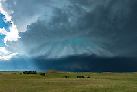 """It was an intimidating sight watching this monster barrel towards me. It's amazing how something can be so beautiful and so destructive at the same time. Within minutes the sky changed from bright and sunny to black and the quiet turned into a roaring wind. This supercell first formed in Montana, before charging southeast along the Black Hills. Enhanced wind shear next to the mountains helped sculpt the clouds into this ominous structure. 2 tornadoes were reported, the first knocked down swaths of forest, while the second destroyed buildings farther east. Experts disagree on why exactly some storms appear green. But it is a good indication that a storm reaches high into the atmosphere and contains much precipitation, which often includes hail. At the time of this shot hail stones 3-4"""" in diameter were falling just a few miles away in downtown Rapid City. As much as I wanted to stay and time lapse this scene, I continued to flee south instead out of the damage path. I've found my windshield to be more effective when it stays in one piece."""