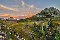 The sky lights up with the colors of sunset over Hidden Lake Pass. This is a short hike from Logan Pass and the peak underneath the moon is Heavy Runner Mountain.