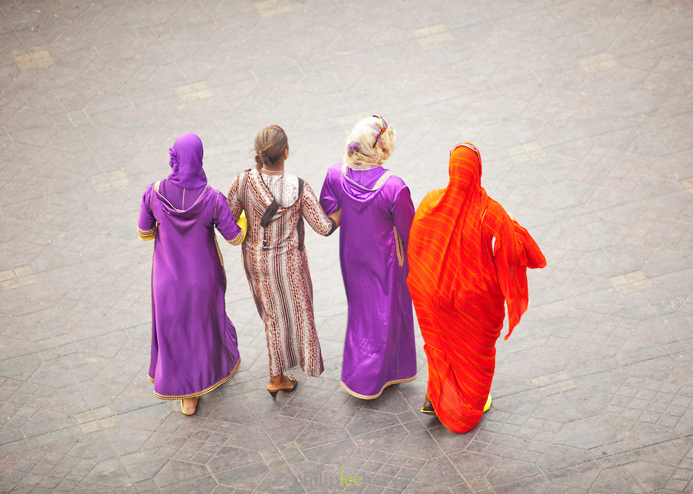 Women walk into the Djemaa el Fna in the medina of Marrakech, Morocco