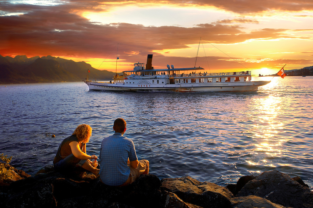 Youg couple watching a ferry at sunset on Lac Leman (lake Geneva) - Montraux Switzerland