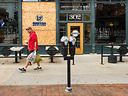 31 MAY 2020 - DES MOINES, IOWA: A man walks by a sports bar that had a window shattered by rioters in downtown Des Moines very early Sunday morning. A group of rioters, protesting the death of George Floyd in police custody in Minneapolis, smashed windows in businesses and restaurants around the Polk County Courthouse in Des Moines. Des Moines police said they made 25 arrests Saturday night and very early Sunday morning. No one was hurt in the disturbances.     PHOTO BY JACK KURTZ