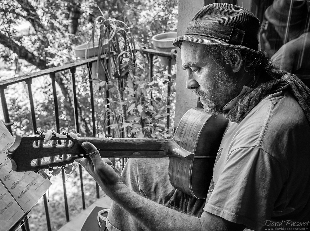 This guitarists plays for street audience from his balcony.