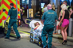 © Licensed to London News Pictures . 15/06/2014 . Manchester , UK . A woman is carried on a trolley in to a waiting ambulance . People on a night out in Manchester City Centre overnight , following England's defeat to Italy in the World Cup . Photo credit : Joel Goodman/LNP