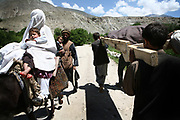 An Afghan woman in a burqa, at left, glances at the dead body of Qamar, a 26-year-old tuberculosis patient who died of complications two weeks after the delivery, as relatives and volunteers carry the body on foot for 10 km due to road closures to her village in Shohada district in Badakshan province, Afghanistan, Monday, May 21, 2007.