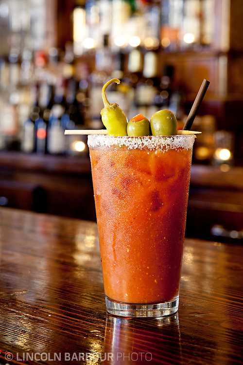 A pristine looking Bloody Mary stands on a wooden bar. Many other bottles of alcohol are out of focus in the background.