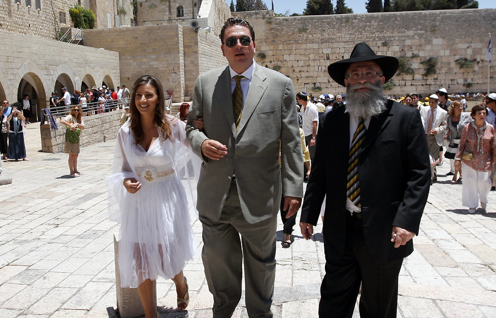 Miki Dorsman, owner and coach of Israeli basketball club Hapoel Holon (C) and his wife Tali Zaks are accompanied by Rabbi Yaakov Gliberman, following their wedding ceremony at the Western Wall, Judaism's holiest site in the Old City of Jerusalem, on June 13, 2008.