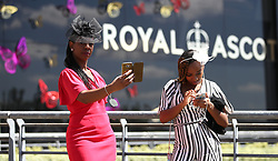 A female racegoer takes a selfie during day four of Royal Ascot at Ascot Racecourse.