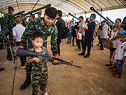 """14 JANUARY 2017 - BANGKOK, THAILAND: A Thai soldier helps a child hold an empty Royal Thai Army  M-16A1 assault rifle during Children's Day activities at the King's Guard, 2nd Cavalry Division base in Bangkok. Thailand National Children's Day is celebrated on the second Saturday in January. Known as """"Wan Dek"""" in Thailand, Children's Day is celebrated to give children the opportunity to have fun and to create awareness about their significant role towards the development of the country. Many government offices open to tours and military bases hold special children's day events. It was established as a holiday in 1955.       PHOTO BY JACK KURTZ"""