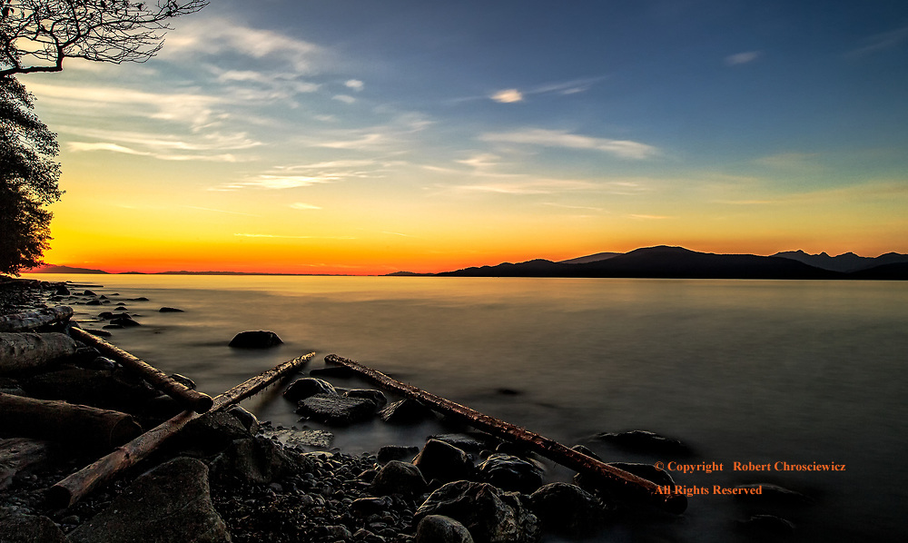 Acadian Autumn: Sunset from a driftwood strewn, rocky Acadian Beach, Vancouver British Columbia, Canada.<br /> <br /> <br /> .