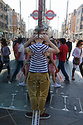 A moment of reflected symmetry as a young man in a striped shirt makes a smartphone call in a busy London street. As other shopping pedestrians pass-by in late-afternoon sunshine on London's Long Acre (Street) the young man holds the phone with his right hand while holding himself around the chest with the left. Above his head is the London Underground sign of the Covent Garden station.