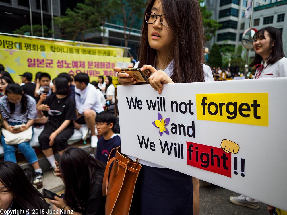 """SEOUL, SOUTH KOREA: A South Korean woman with a placard during the Wednesday protest at the Japanese embassy in Seoul. The Wednesday protests have been taking place since January 1992. Protesters want the Japanese government to apologize for the forced sexual enslavement of up to 400,000 Asian women during World War II. The women, euphemistically called """"Comfort Women"""" were drawn from territories Japan conquered during the war and many came from Korea, which was a Japanese colony in the years before and during the war. The """"comfort women"""" issue is still a source of anger of many people in northeast Asian areas like South Korea, Manchuria and some parts of China.   PHOTO BY JACK KURTZ   <br /> Wednesday Demonstration demanding Japan to redress the Comfort Women problems"""