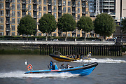 High-speed boats with the 'Thames Jet Extreme' and 'Thames Rib Experience' pass each other on the river Thames near Canary Wharf in London Docklands, on 16th September 2021, in London, England.