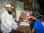 01 JUNE 2015 - KULAI, JOHORE, MALAYSIA:  An Imam teaches Rohingya children in a madrasa (Muslim religious school) in Kulai, Malaysia. The Rohingya children are not allowed to attend Malaysian schools. Their madrasa is in a dilapidated building with holes in the roof and exposed wiring. The UN says the Rohingya, a Muslim minority in western Myanmar, are the most persecuted ethnic minority in the world. The government of Myanmar insists the Rohingya are illegal immigrants from Bangladesh and has refused to grant them citizenship. Most of the Rohingya in Myanmar have been confined to Internal Displaced Persons camp in Rakhine state, bordering Bangladesh. Thousands of Rohingya have fled Myanmar and settled in Malaysia. Most fled on small fishing trawlers. There are about 1,500 Rohingya in the town of Kulai, in the Malaysian state of Johore. Only about 500 of them have been granted official refugee status by the UN High Commissioner for Refugees. The rest live under the radar, relying on gifts from their community and taking menial jobs to make ends meet. They face harassment from Malaysian police who, the Rohingya say, extort bribes from them.       PHOTO BY JACK KURTZ