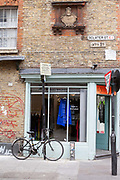 Details of a shop on the corner of Sclater Street and Brick Lane that shows, Huguenot, Bangladeshi and contemporary sineage