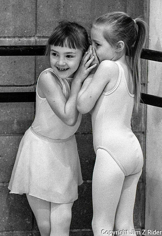 Two tiny dancers share a bit of gossip during a ballet class.