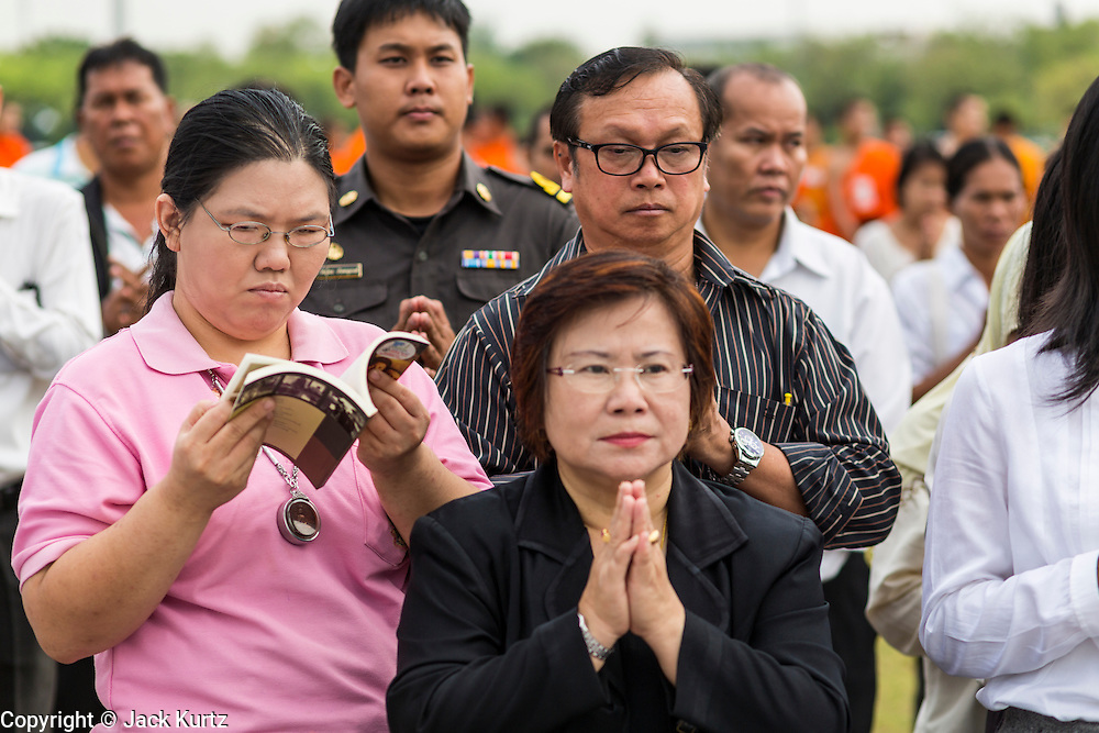 "23 APRIL 2013 - BANGKOK, THAILAND:   A Thai woman reads while everyone around her prays during the opening ceremony to mark Bangkok as the World Book Capital City 2013. UNESCO awarded Bangkok the title. Bangkok is the 13th city to assume the title of ""World Book Capital"", taking over from Yerevan, Armenia. Bangkok Governor Suhumbhand Paribatra announced plans that the Bangkok Metropolitan Administration (BMA) intends to encourage reading among Thais. The BMA runs 37 public libraries in the city and has modernised 14 of them. It plans to build 10 more public libraries every year. Port Harcourt, Nigeria will be the next World Book Capital in 2014.<br /> PHOTO BY JACK KURTZ"