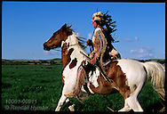 Plains Indian reenactor Mike Terry in Cheyenne headdress and Blackfoot clothes rides bareback at Fort Union National Historic Site, North Dakota